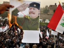 מפגינים עירקים מעלים באש פוסטר של עיזת איברהים א-דורי [צילום: AP]