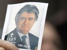 רדובן קרדז'יץ' כפי שנראה בעת מנהיגותו (צילום של אשה המחזיקה בתמונה בעת הפגנות בבלגרד השבוע) [צילום: AP]