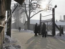 """מבקרים חולפים על פני השלט שהוצב במקום השלט המקורי """"העבודה משחררת"""" באושוויץ [צילום: AP]"""