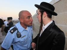 קצין משטרה מול מפגין חרדי [צילום: פלאש 90]