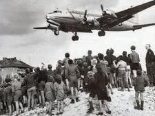 ברלינאים מביטים במטוס תובלה דאגלס C-54 סקיימאסטר) אמריקאי הנוחת בשדה התעופה של מערב ברלין (טמפלהוף)