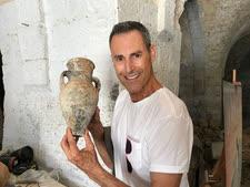 אורי גלר מחזיק קנקן לאגירת מים או שמן שנתגלה במהלך העבודות במוזיאון [צילום: דלילה בר רצון]