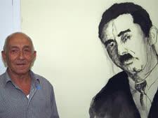 """יעקב שרת עומד ליד ציור פרוטרט של אביו משה שרת 2001 [צילום: משה מילנר/לע""""מ]"""