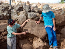 ילדים מחיספין המתנדבים בחפירה, מצביעים על הדמויות שחרותות על האבן [צילום: יניב ברמן, רשות העתיקות]