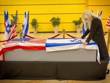האלמנה מרים אדלסון  לצד ארון בעלה[צילום: עמי שומן/ישראל היום]