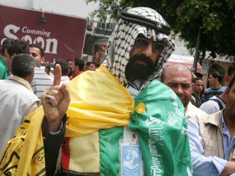 פלשתיני בעזה לבוש דגל חמאס ודגל פתח. אחדות במטרה המשותפת נגד ישראל  [צילום: פלאש 90]